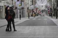 A couple takes a selfie on a quiet New Bond Street in London, Saturday, Dec. 26, 2020. London is currently in Tier 4 with all non essential retail closed and people have been asked to stay at home, on what is usually one of the busiest retail days of the year with the traditional Boxing Day sales in shops. (AP Photo/Kirsty Wigglesworth)