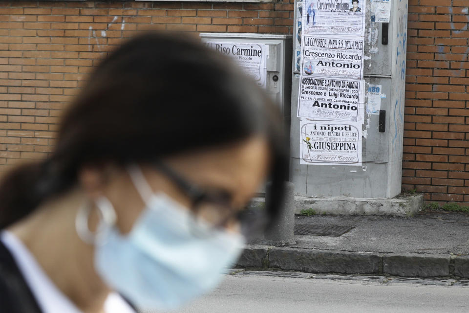 A woman walks past obituaries posted outside the San Giuliano hospital in Giugliano in the outskirts of Naples, Italy, Saturday, Nov. 14, 2020. The pandemic has heightened the urgency of the plight of those seeking medical care in public hospitals in Italy's economically under-developed south. (AP Photo/Gregorio Borgia)