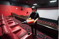 <p>Kyle Curtis cleans a the theater with an electrostatic disinfectant spray machine at the AMC Highlands Ranch 24 on August 20 in Highlands Ranch, Colorado.</p>