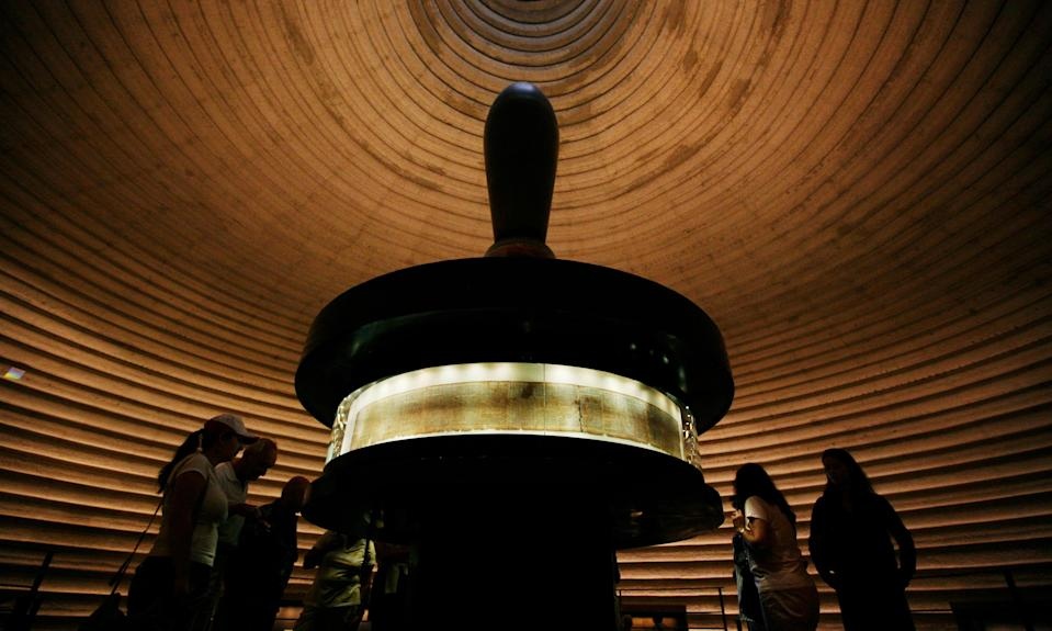 Tourists look at portions of the Dead Sea scrolls on display at the Shrine of the Book in Jerusalem (PIcture Getty)