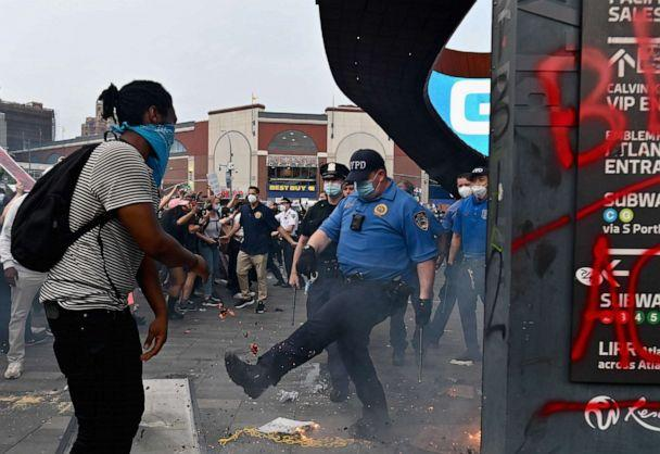 PHOTO: A police officer gestures near a small fire burning as protesters gather for a 'Black Lives Matter' protest near Barclays Center on May 29, 2020 in Brooklyn, New York, after George Floyd died while being arrested by a police officer in Minneapolis. (Angela Weiss/AFP via Getty Images)