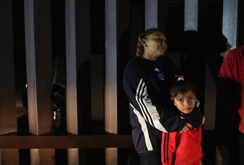 A Honduran mother stands with her family at the U.S.-Mexico border fence on Feb. 22, 2018, near Penitas, Texas.