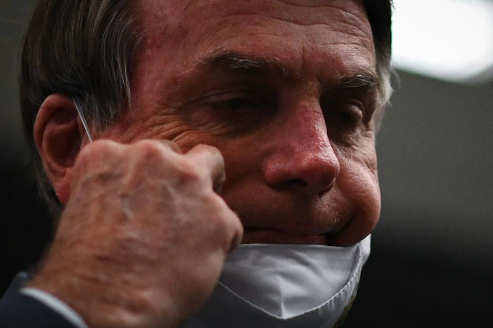 Brazil's President Jair Bolsonaro removes his protective face mask to speak to journalists during a press conference amidst the Coronavirus (COVID-19) pandemic at Galeao Airport in Rio de Janeiro, Brasil, on May 5, 2021. (Photo by Andre Borges/NurPhoto via Getty Images)