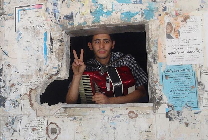 Ayham al-Ahmed, a resident of Damascus' Yarmuk Palestinian refugee camp, poses with his accordion on June 26, 2014 (AFP Photo/Rami Al-Sayed)