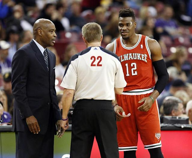 Official Bill Spooner talks with Milwaukee Bucks head coach Larry Drew, left, and forward Jeff Adrien, after Adrien was called for a foul during the first quarter of an NBA basketball game against the Sacramento Kings in Sacramento, Calif., Sunday, March 23, 2014. (AP Photo/Rich Pedroncelli)