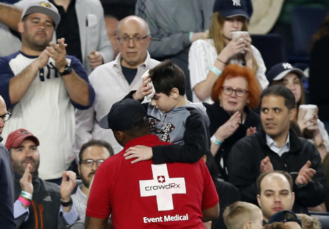 Fans applaud as a medical employee carries an injured youngster from the stands after the boy was hit in the head by a shattered bat at a Royals-Yankees game in May of 2017. (AP)