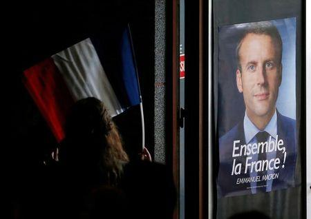 A supporter holds a French flag next to a poster of Emmanuel Macron, a head of the political movement En Marche !, or Onwards !, and a candidate for the 2017 presidential election, during his campaign rally in Chatellerault, France, April 28, 2017. REUTERS/Regis Duvignau