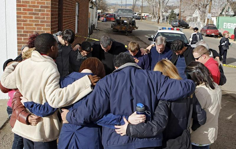Members of a community church gather in a prayer circle a block from where a woman and two children were found dead and a third child wounded in the Globeville neighborhood in Denver on Wednesday, Feb. 6, 2013.  The shooting appeared to have been isolated and there was no indication a shooter is on the loose, police Major Crimes Cmdr. Ron Saunier said.  (AP Photo/Ed Andrieski)