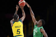 Nigeria's Caleb Agada (3) tries to block a shot by Australia's Patty Mills (5) during a men's basketball preliminary round game at the 2020 Summer Olympics, Sunday, July 25, 2021, in Saitama, Japan. (AP Photo/Charlie Neibergall)
