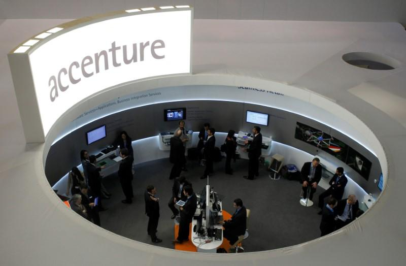 Visitors look at devices at Accenture stand at the Mobile World Congress in Barcelona