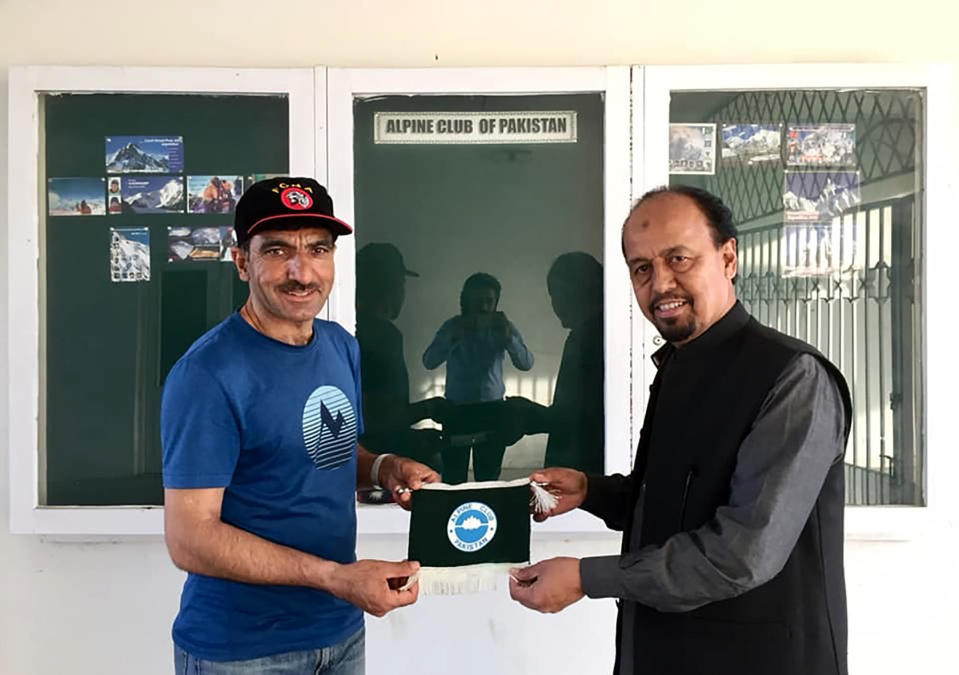 In this 2018 photo provided by Alpine Club of Pakistan shows, Pakistani mountaineer Ali Sadpara, left, receives a souvenir from Karrar Haider, a top official of Alpine Club of Pakistan, at his office in Islamabad, Pakistan. An aerial search mission is on to find three experienced climbers, Sadpara and his two companions, John Snorri and Juan Pablo Mohr, who lost contact with the base camp during their ascend on world's second top peak in northern Pakistan, official said Sunday, Feb. 7, 2021. (Alpine Club of Pakistan via AP)