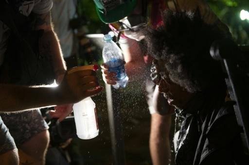 Protestors wash their eyes with water after being sprayed by tear gas in Washington, May 31, 2020