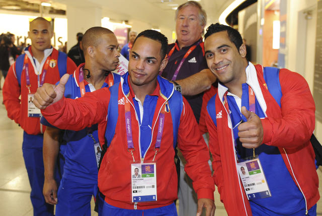 Members of the Cuban weightlifting squad arrive at Heathrow airport, London, July 16, 2012. The London 2012 Olympic Games start in 11 days time. REUTERS/Paul Hackett (BRITAIN - Tags: SPORT OLYMPICS)