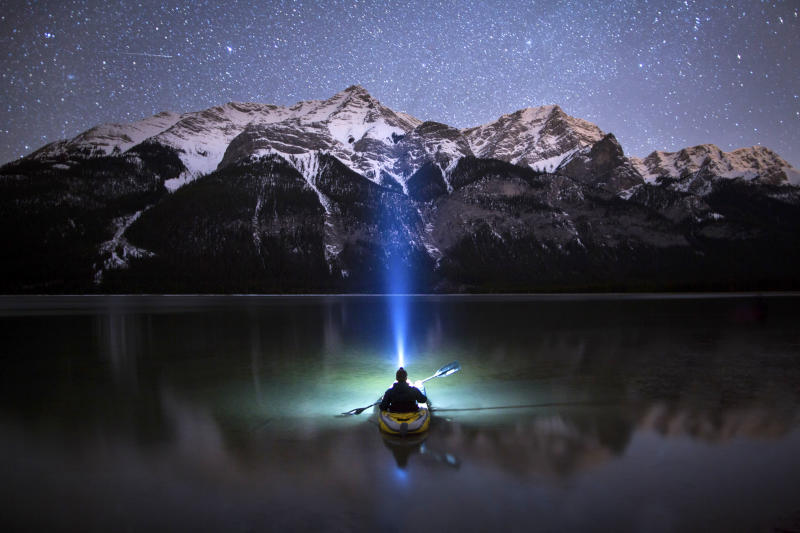 Paul Zizka Drifts across a lake in the Canadian Rockies a beam from his head lamp shooting up into the night sky in the Canadian Rockies. (Photo: Paul Zizka/Caters News)
