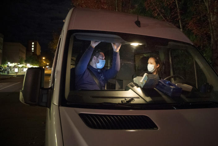 In this Oct. 2020 photo, Crisis Workers, Emergency Medical Technicians (EMTs), Henry Cakebread and Ashley Barnhill-Hubbard with CAHOOTS, a mental health crisis intervention program, discuss their last encounter during their night shift in Eugene, Ore. When police respond to a person gripped by a mental health or drug crisis, the encounter can have tragic results. Now a government health program will help communities set up an alternative: mobile teams of practitioners trained in de-escalating such potentially volatile situations. (William Holderfield via AP)