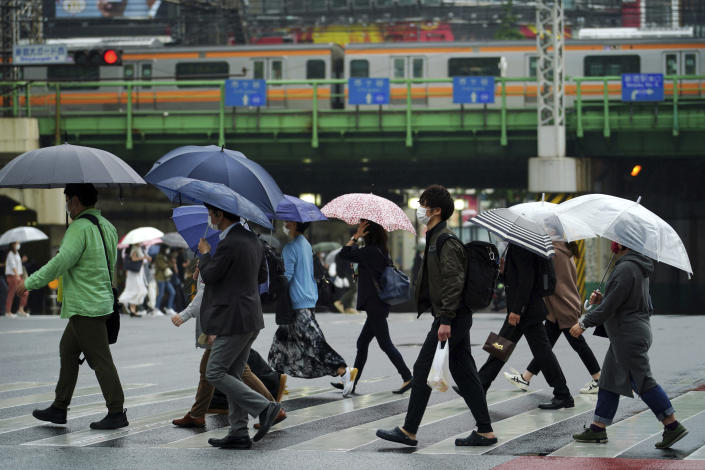People wearing protective masks to help curb the spread of the coronavirus walk along a pedestrian crossing Thursday, May 13, 2021, in Tokyo. The Japanese capital confirmed more than 1,000 new coronavirus cases on Thursday. (AP Photo/Eugene Hoshiko)