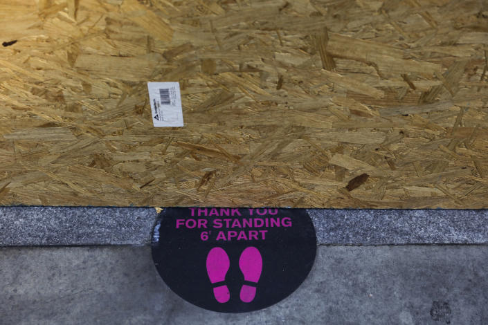 A sign advising to social distance is partially covered by a plywood panel protecting a restaurant from potential vandalism Wednesday, June 3, 2020, in downtown Los Angeles. (Jae C. Hong/AP)