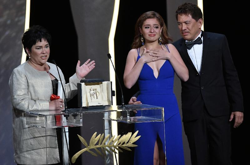 Filipino actress Jaclyn Jose (L) celebrates on stage next to her daughter, actress Andi Eigenmann, and Filipino director Brillante Mendoza after being awarded with the Best Actress prize during the closing ceremony of the 69th Cannes Film Festival (AFP Photo/Alberto Pizzoli)