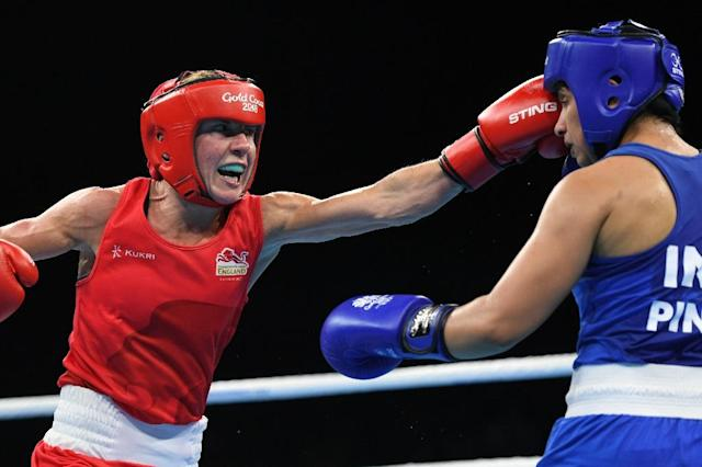 England's Lisa Whiteside (in red) fights India's Pinki Rani (in blue) during their women's 51kg category quarter-final boxing match (AFP Photo/YE AUNG THU)