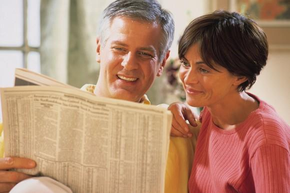 A smiling married couple reading the financial portion of a newspaper.