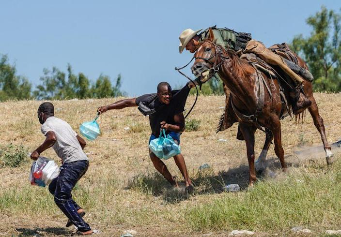 A United States Border Patrol agent on horseback tries to stop a Haitian migrant from entering an encampment on the banks of the Rio Grande near the Acuna Del Rio International Bridge in Del Rio, Texas on September 19, 2021. - The United States said Saturday it would ramp up deportation flights for thousands of migrants who flooded into the Texas border city of Del Rio, as authorities scramble to alleviate a burgeoning crisis for President Joe Biden's administration. (Photo by PAUL RATJE / AFP) (Photo by PAUL RATJE/AFP via Getty Images)