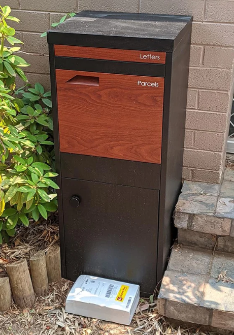 Pictured is a package on the ground next to a mailbox.