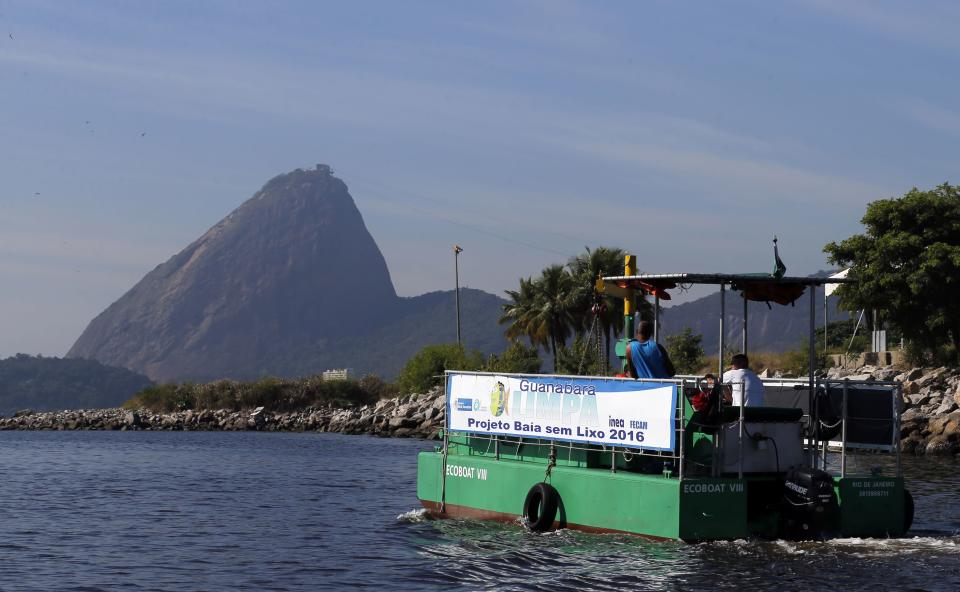 """A garbage collecting boat in seen in front of the Sugar Loaf mountain at the Guanabara Bay in Rio de Janeiro March 12, 2014. According to the local media, the city of Rio de Janeiro continues to face criticism locally and abroad that the bodies of water it plans to use for competition in the 2016 Olympic Games are too polluted to host events. Untreated sewage and trash frequently find their way into the Atlantic waters of Copacabana Beach and Guanabara Bay - both future sites to events such as marathon swimming, sailing and triathlon events. The banner reads """"Project Bay without garbage"""". Picture taken on March 12, 2014. REUTERS/Sergio Moraes (BRAZIL - Tags: ENVIRONMENT SPORT OLYMPICS)"""