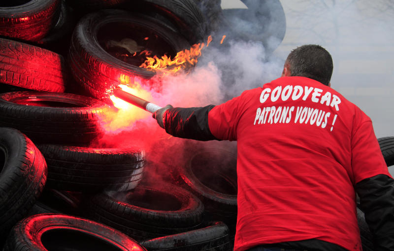 """Goodyear employee burns tires, outside the Goodyear tyre company, in Amiens, northern France, Tuesday Feb. 26, 2013. Workers at a dying French tire factory who've become the butt of American jokes are staging a day of last-ditch protests to try to save their jobs. The protests in the northern city of Amiens come after efforts to find a new buyer for the struggling plant have fizzled. An American executive who considered buying it sent a letter last week to the French government saying that France's economic model is too worker-friendly and discourages investment. The words on the shirt translates to """"Bosses from Hell """".(AP Photo/Michel Spingler)(AP Photo/Michel Spingler)"""