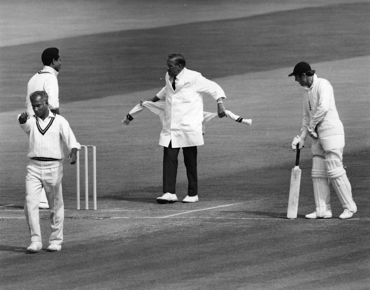 11th August 1973:  Umpire Arthur Fagg prepares to tie a jumper around his waist. He had earlier quit the field after a player refused to apologise to him and he had to be persuaded back.  (Photo by Central Press/Getty Images)