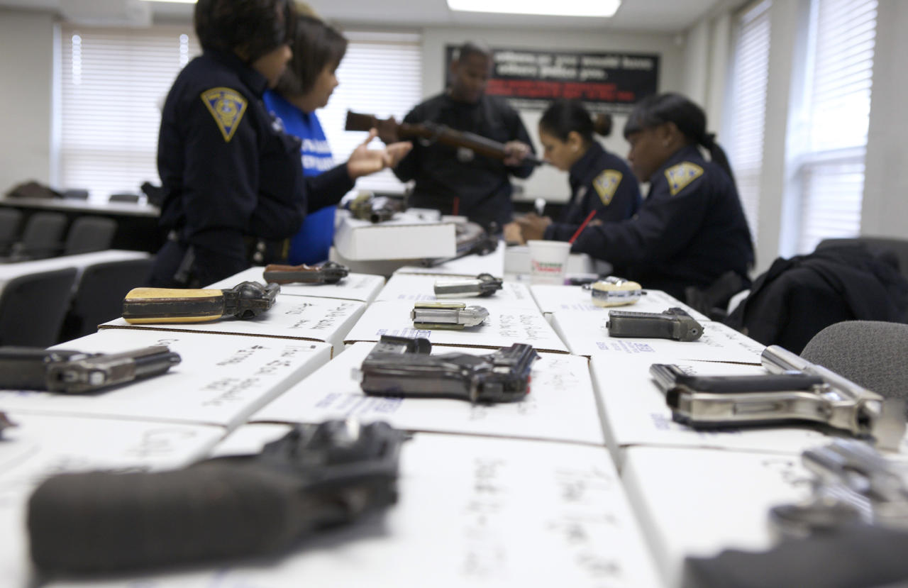New Haven police officers catalogue guns being turned in during a gun buyback event at the New Haven Police Academy in New Haven, Connecticut, December 22, 2012. The program, sponsored by the Injury Free Coalition for Kids of New Haven and Yale-New Haven Children's Hospital, offered gift cards in exchange for working guns.  REUTERS/ Michelle McLoughlin (UNITED STATES - Tags: SOCIETY)