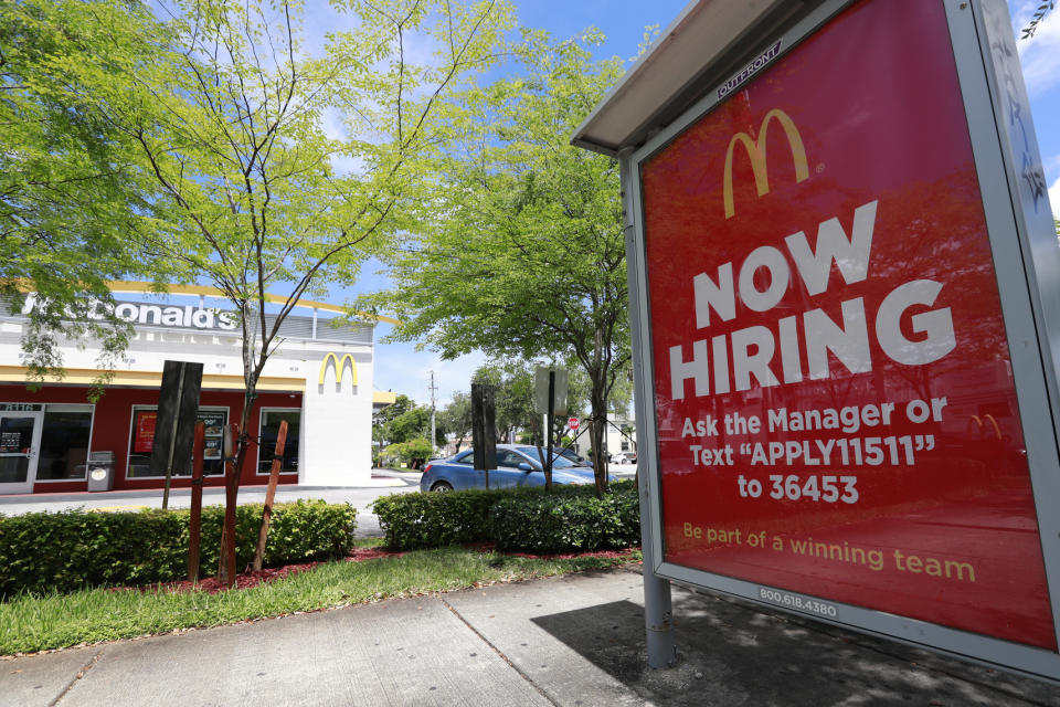 In this Monday, July 1, 2019 photo, a help wanted sign appears on a bus stop in front of a McDonald's restaurant in Miami. On Tuesday, July 9, the Labor Department reports on job openings and labor turnover for April. (AP Photo/Wilfredo Lee)