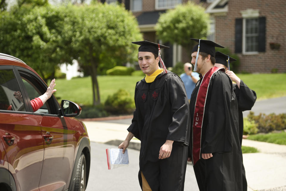 College graduates watch as friends parade by to congratulate them on Saturday, May 16, 2020. (Photo: Lauren A. Little/MediaNews Group/Reading Eagle via Getty Images)