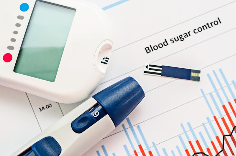 Glucometer and insulin pen on top of a paper with the words Blood sugar control.