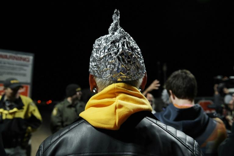 """Attendee Daniel Rodriguez wears a tinfoil hat as he and other Alien hunters gathered to """"storm"""" Area 51 at an entrance near Rachel, Nevada"""
