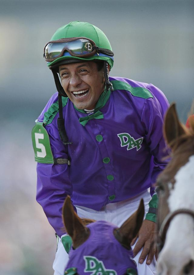 Victor Espinoza smiles after riding California Chrome to a victory during the 140th running of the Kentucky Derby horse race at Churchill Downs Saturday, May 3, 2014, in Louisville, Ky. (AP Photo/Darron Cummings)