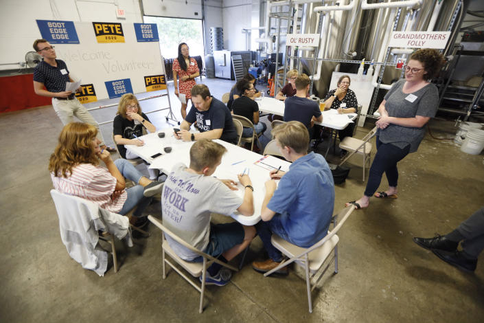 """Supporters for Democratic presidential candidate Pete Buttigieg meet at a local brewery for a """"relational phone bank"""", Thursday, Aug. 29, 2019, in West Des Moines, Iowa. The group worked their smartphones calling and texting friends to test their interest in the candidate. Buttigieg is well behind his better known rivals in Iowa who have spent months building a deep organizational structure in the state that marks the first test for the Democratic presidential nomination. But thanks to his campaign taking in nearly $25 million in contributions in the last quarter, money that he is using to help create an army of peer-to-peer foot soldiers, Buttigieg is rapidly trying to catch up. (AP Photo/Charlie Neibergall)"""