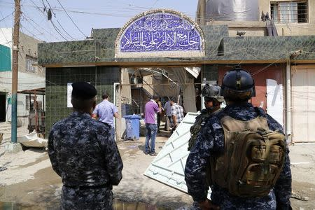 Iraqi security forces stand guard outside a Shi'ite mosque after a suicide bomb attack in the New Baghdad district