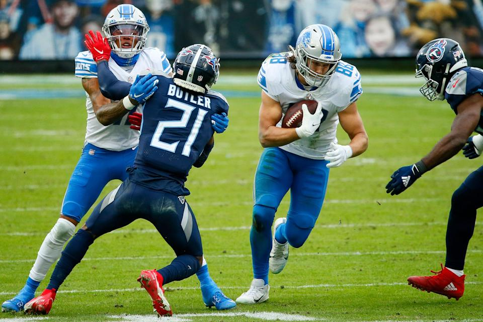 Tight end T.J. Hockenson of the Detroit Lions carries the football as wide receiver Marvin Jones, left, of the Detroit Lions blocks cornerback Malcolm Butler (21) of the Tennessee Titans during the second quarter of the game at Nissan Stadium on Dec. 20, 2020, in Nashville, Tennessee.