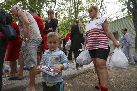 Ukrainian refugees from the Donetsk region receive food as humanitarian aid on the outskirts of the southern coastal town of Mariupol September 10, 2014. REUTERS/Vasily Fedosenko