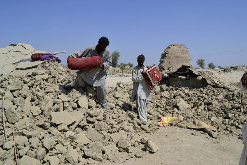 Survivors of earthquake collect their belongings near rubble of mud house after it collapsed following the quake in the town of Awaran