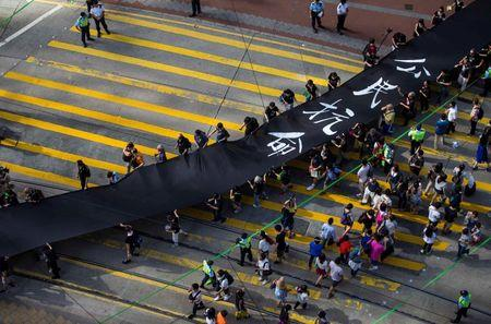 Occupy Central protesters march with 500-meter long black cloth, which they say symbolizes the loss of credibility in Beijing's refusal to allow true democracy in Hong Kong, September 14, 2014. REUTERS/Tyrone Siu