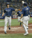 Tampa Bay Rays on-deck hitter Brandon Lowe (8) congratulates Joey Wendle, left, as he scores on a two-run double hit by Kevin Kiermaier off Miami Marlins reliever Dean Guenther during the fourth inning of a baseball game Friday, Sept. 24, 2021, in St. Petersburg, Fla. (AP Photo/Steve Nesius)