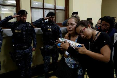 Relatives of a slain policeman react during a homage for their loved one and two colleagues, who were killed during an attack, at the headquarters of the Civil National Police in Guatemala City