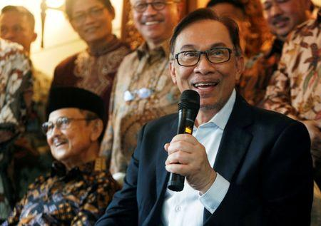 FILE PHOTO: Malaysian politician Anwar Ibrahim speaks with the media as former Indonesian President B.J. Habibie looks on during a visit to Habibie's home in Jakarta