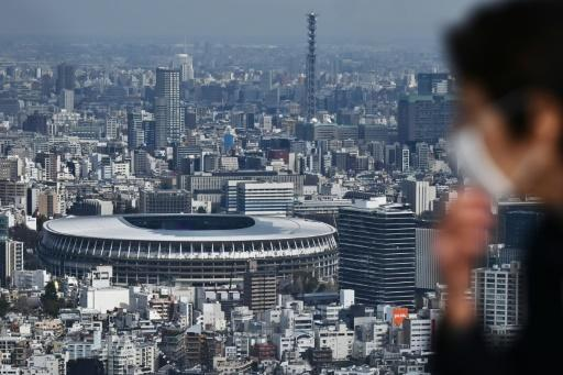 A man wearing a face mask looks out at the main Olympic Stadium in Tokyo where the track and field is due to take place