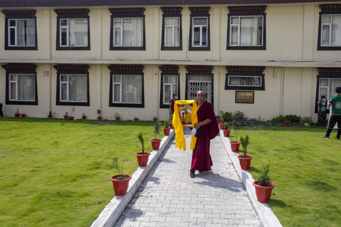 An exile Tibetan monk carries a portrait of his spiritual leader the Dalai Lama as he celebrates the 86th birthday of the Tibetan leader in Dharmsala, India, Tuesday, July 6, 2021. The Dalai Lama made the hillside town of Dharmsala his headquarters after a failed uprising against Chinese rule in 1959. (AP Photo/Ashwini Bhatia)