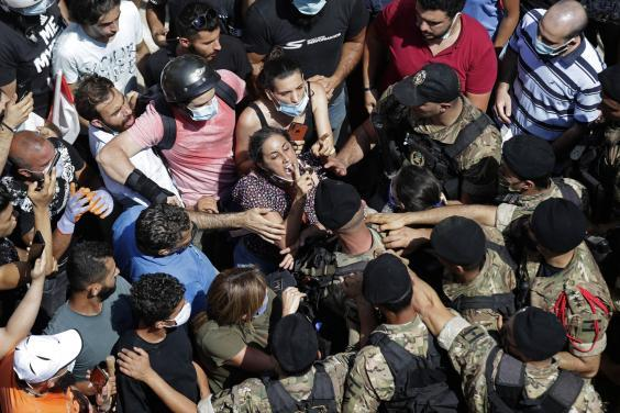 A woman yells during scuffles with soldiers blocking a Beirut road as French president Emmanuel Macron visits the Gemmayzeh neighborhood (AP)