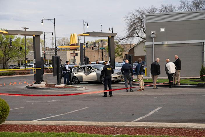 <p>Police investigate a crime scene where Jontae Adams, 28, and his daughter Jaslyn, 7, were shot, resulting in Jaslyn's death at a McDonald's drive-thru, on 18 April 18, 2021, in Chicago</p> (Chicago Sun-Times via AP)