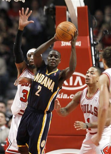 Indiana Pacers guard Darren Collison (2) looks to pass between the Chicago Bulls' defense of guard Richard Hamilton (32) and guard Derrick Rose (1) during the first half of an NBA basketball game on Wednesday, Jan. 25, 2012, in Chicago. (AP Photo/Charles Rex Arbogast)
