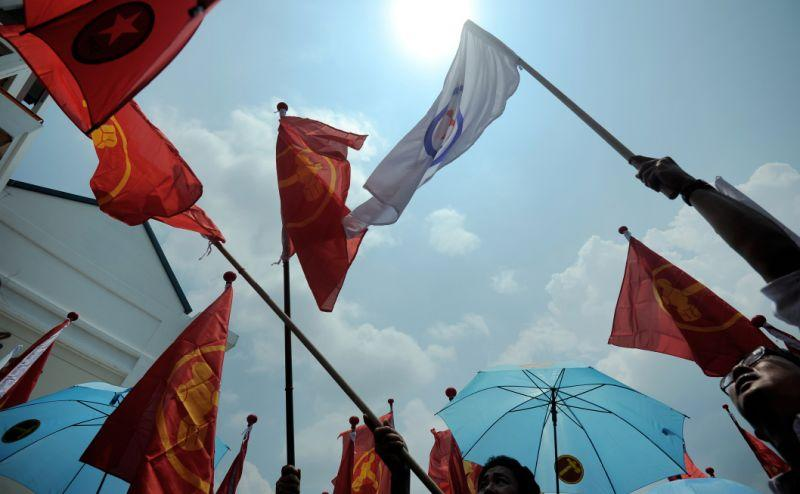 Supporters of various political parties display party flags on Nomination Day on September 1, 2015. (Photo: MOHD FYROL/AFP via Getty Images)